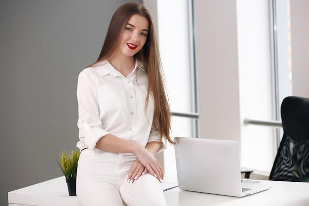 Szczęśliwy bizneswoman, opierając się na biurku w biurze