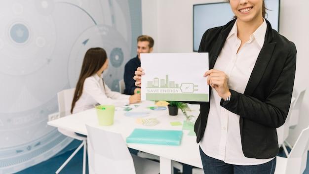 Szczęśliwy bizneswoman pokazuje energooszczędnego pojęcie na papierze