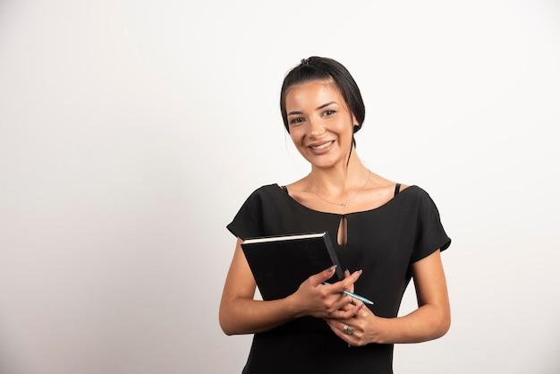 Szczęśliwy bizneswoman pozuje z notatnikiem na białej ścianie.