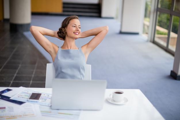 Szczęśliwy bizneswoman relaksuje przy biurkiem