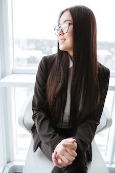 Szczęśliwy bizneswoman siedzi w szkłach i patrzeje okno