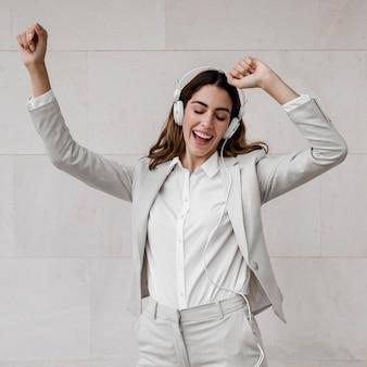 Szczęśliwy bizneswoman, słuchanie muzyki na słuchawkach