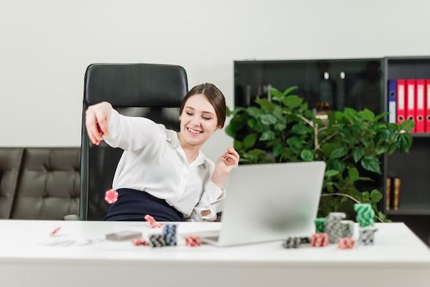 Szczęśliwy bizneswoman wygrywa w kasynie online podczas gdy bawić się grzebaka w biurze przy miejscem pracy