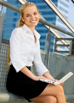 Szczęśliwy bizneswoman z laptopem w mieście