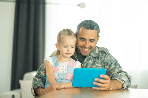 Szczęśliwy blisko tatusia. śliczna blond córka czuje się szczęśliwa siedząc obok tatusia i oglądając kreskówkę