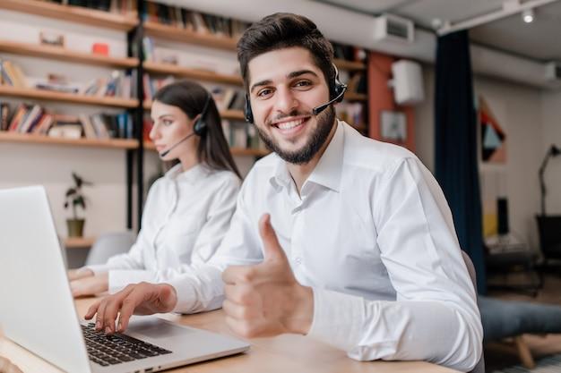 Szczęśliwy bliskowschodni centrum telefoniczne operator uśmiecha się aprobaty w biurze i pokazuje