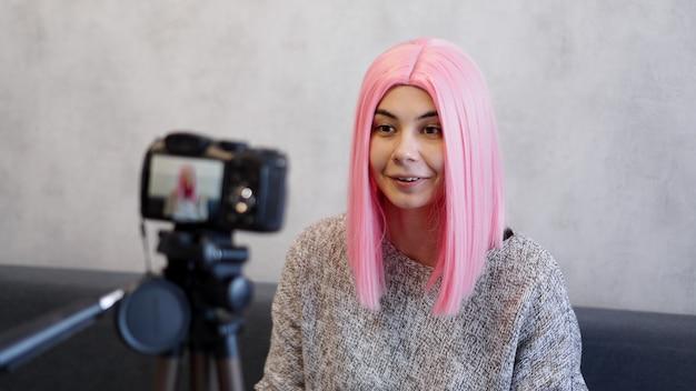 Szczęśliwy bloger w różowej peruce przed aparatem na statywie. nagrywa wideo