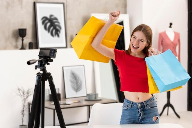 Szczęśliwy blogger trzyma torby na zakupy