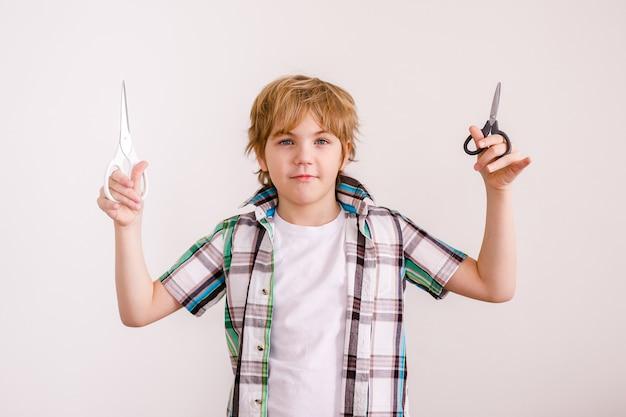 Szczęśliwy blond chłopiec europejski wygląd w białej koszuli trzymając nożyczki