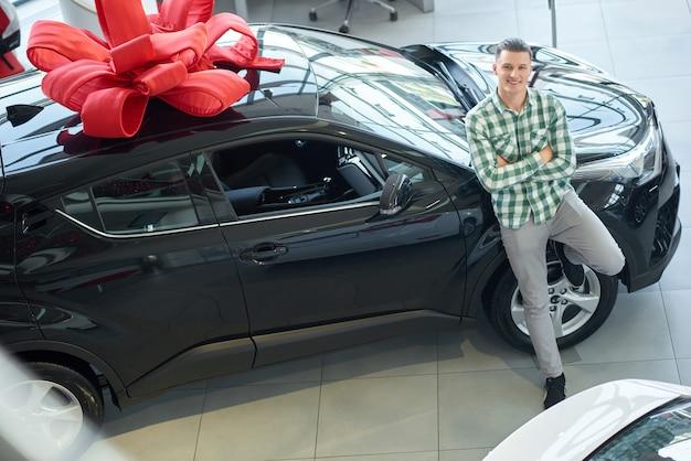 Szczęśliwy blond zwycięzca ono uśmiecha się blisko samochodu z czerwonym łękiem na wierzchołku.
