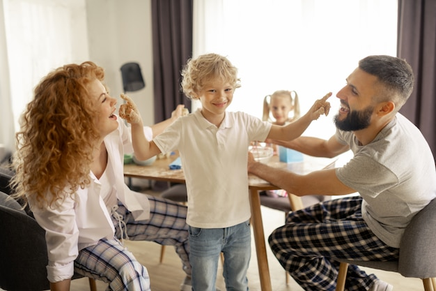 Szczęśliwy blondynka chłopiec stojący między rodzicami