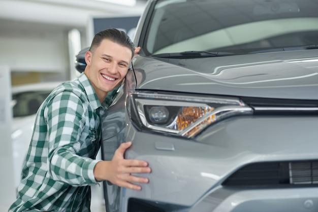 Szczęśliwy blondynka mężczyzna ono uśmiecha się po kupować jego pierwszy samochód.