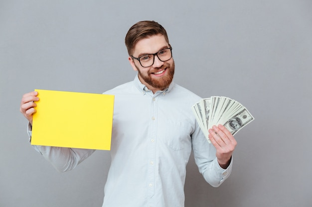 Szczęśliwy brodaty biznesmena mienia copyspace puste miejsce i pieniądze
