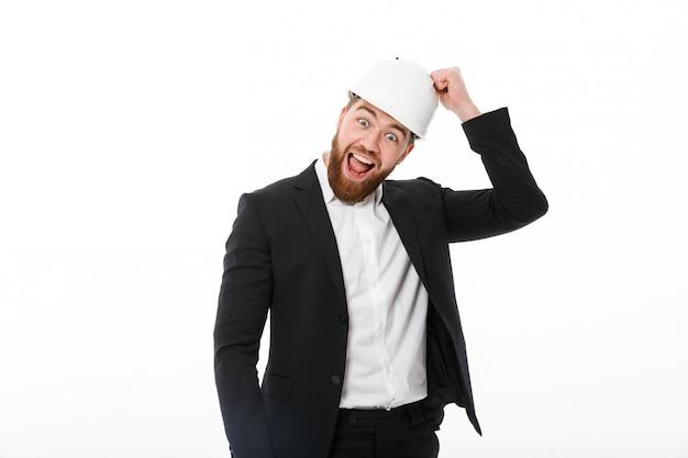 Szczęśliwy brodaty biznesowy mężczyzna w ochronnym hełmie puka na nim