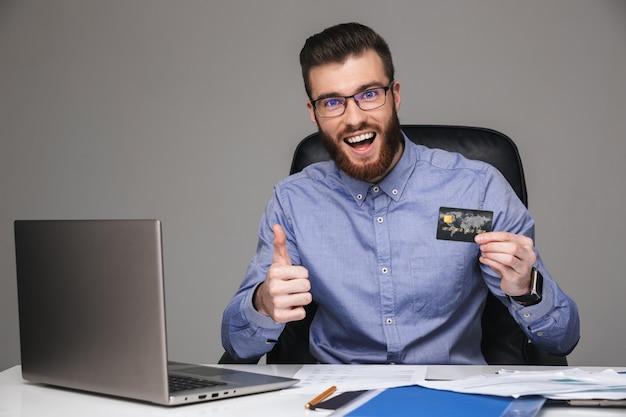 Szczęśliwy brodaty elegancki mężczyzna w okularach pokazujący kciuk do góry i trzymający kartę kredytową, patrząc bezpośrednio siedząc przy stole w biurze