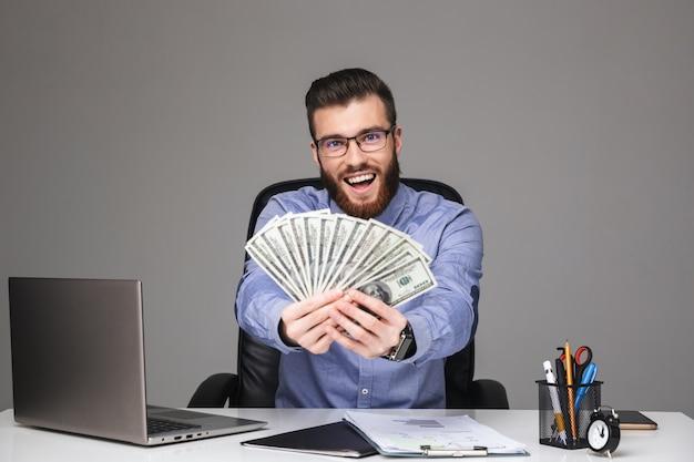 Szczęśliwy brodaty elegancki mężczyzna w okularach pokazujący pieniądze i patrzący bezpośrednio, siedząc przy stole w biurze