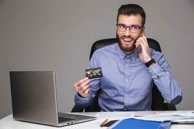 Szczęśliwy brodaty elegancki mężczyzna w okularach rozmawiający przez smartfona i trzymający kartę kredytową siedząc przy stole w biurze