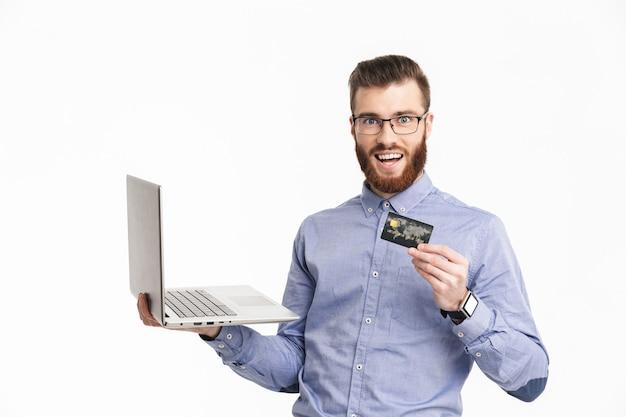Szczęśliwy brodaty elegancki mężczyzna w okularach trzymający laptopa i kartę kredytową podczas patrzenia