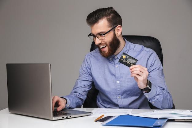 Szczęśliwy brodaty elegancki mężczyzna w okularach z kartą kredytową przy użyciu laptopa siedząc przy stole w biurze