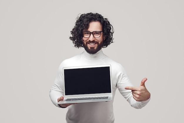 Szczęśliwy Brodaty Facet Pokazujący Laptopa Premium Zdjęcia