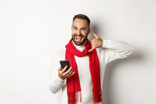 Szczęśliwy brodaty facet trzymający smartfona, pokazujący znak telefonu, proszący o telefon, stojący w świątecznym swetrze i szaliku, białe tło