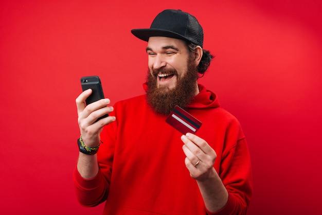 Szczęśliwy brodaty facet używa smartphone i kredytową kartę