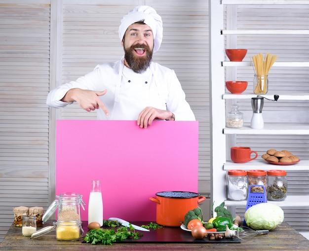 Szczęśliwy brodaty kucharz trzyma różową tablicę do reklamowania profesjonalnego szefa kuchni w kuchni?