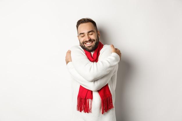 Szczęśliwy brodaty mężczyzna cieszący się wygodnym zimowym swetrem, uśmiechający się ciepło, przytulający się, stojący na białym tle