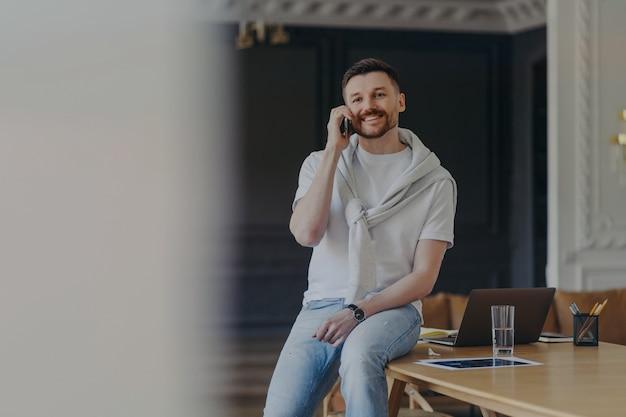 Szczęśliwy brodaty mężczyzna freelancer pracuje w domowym biurze, ubrany w luźną koszulkę i dżinsy, rozmawia przez telefon, omawia problemy związane z pracą, ma wesoły wyraz twarzy, pracuje zdalnie z domu
