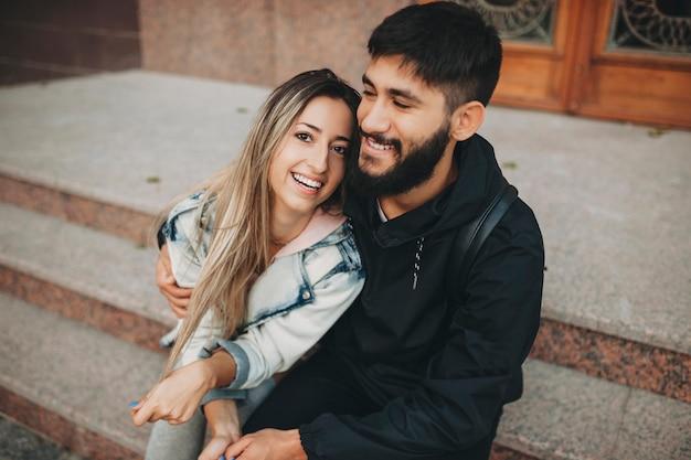Szczęśliwy brodaty mężczyzna i wesoła kobieta obejmując siedząc na schodach na ulicy