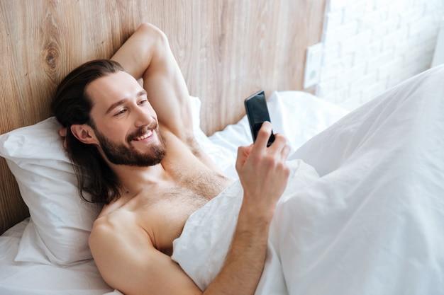 Szczęśliwy brodaty mężczyzna, leżąc w łóżku i przy użyciu telefonu komórkowego