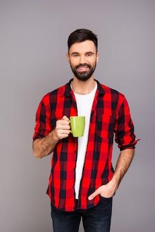 Szczęśliwy brodaty mężczyzna o przerwie i picie herbaty