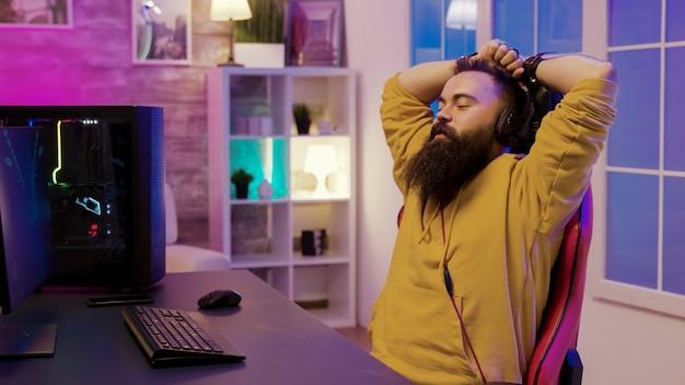 Szczęśliwy brodaty mężczyzna po wygranej w grach online. mężczyzna nosi słuchawki podczas grania w gry wideo.