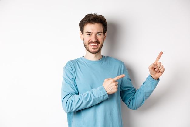 Szczęśliwy brodaty mężczyzna pokazujący reklamę, wskazujący palcami w prawo i uśmiechnięty, zachęcający do kliknięcia linku, stojący na białym tle