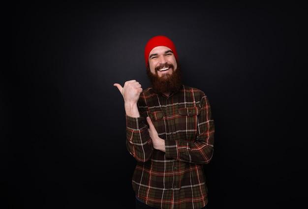Szczęśliwy brodaty mężczyzna pokazuje kciuk up i uśmiech.