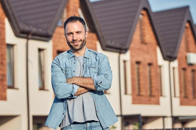 Szczęśliwy brodaty mężczyzna pozuje w pobliżu nowego domu