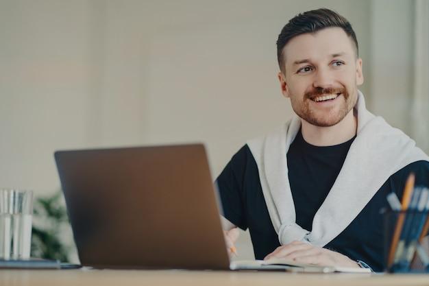 Szczęśliwy brodaty mężczyzna pracownik biurowy pisze plan organizacji działa zdalnie robi notatki z informacjami siedzi przed otwartym laptopem odwraca wzrok ubrany w luźną koszulkę i sweter zawiązany na ramionach