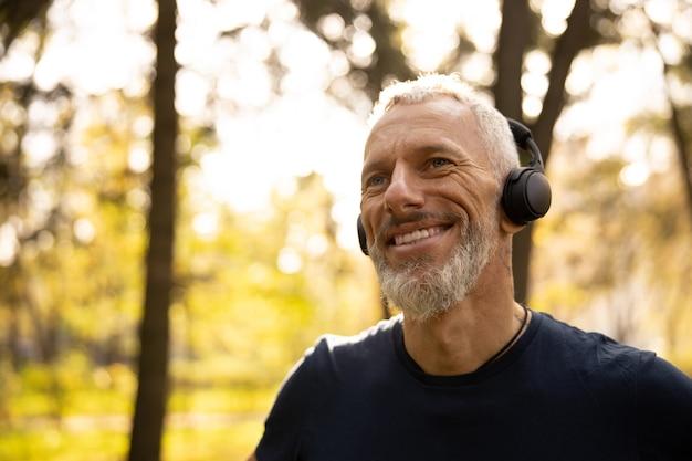 Szczęśliwy brodaty mężczyzna słuchający muzyki w przyrodzie