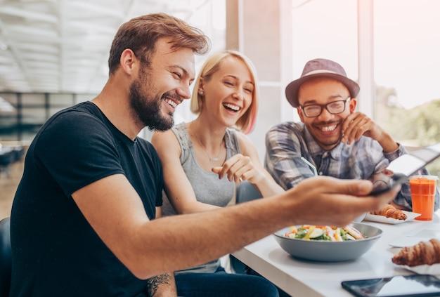 Szczęśliwy brodaty mężczyzna śmiejący się z wielorasowymi przyjaciółmi