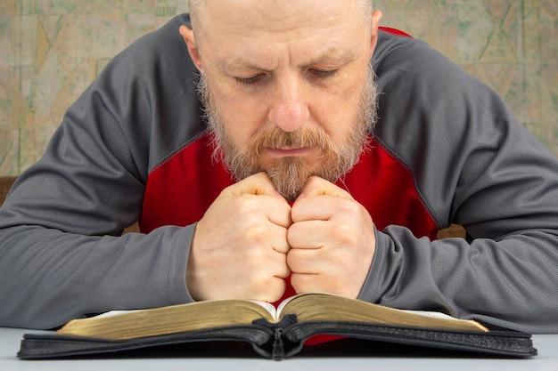 Szczęśliwy, brodaty mężczyzna studiuje biblię. religia i chrześcijaństwo.