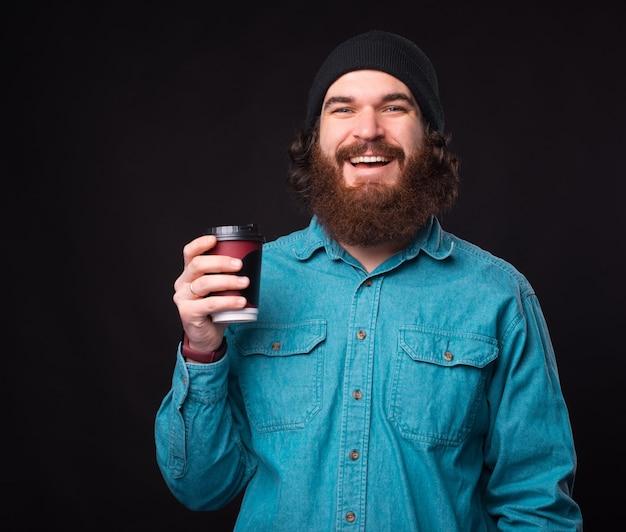 Szczęśliwy brodaty mężczyzna trzyma filiżankę kawy, aby przejść na ciemnym tle