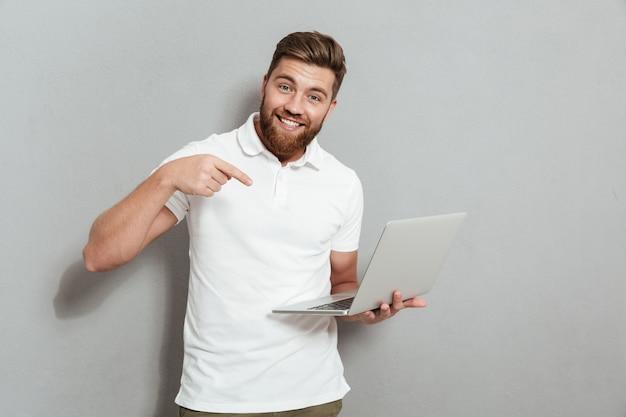Szczęśliwy brodaty mężczyzna trzyma laptop