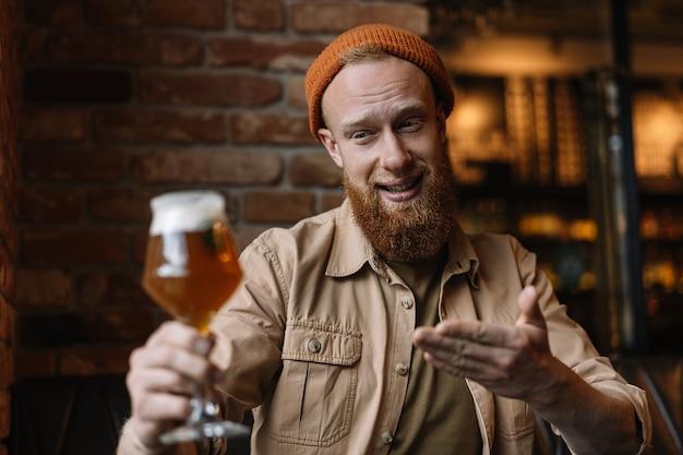 Szczęśliwy brodaty mężczyzna trzyma szkło z piwem
