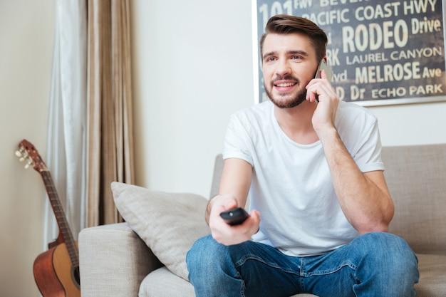 Szczęśliwy brodaty mężczyzna używający pilota i rozmawiający przez telefon komórkowy na kanapie w domu
