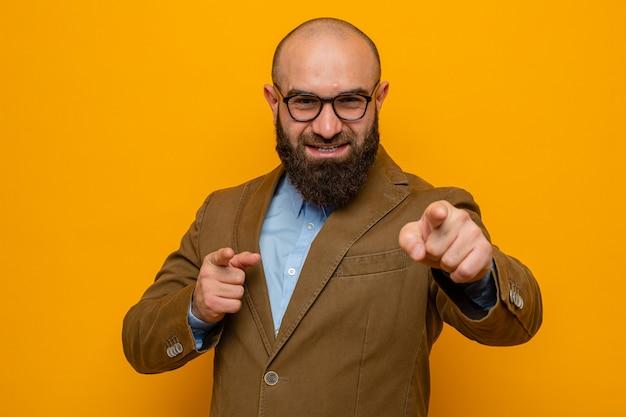 Szczęśliwy brodaty mężczyzna w brązowym garniturze w okularach patrzący uśmiechnięty radośnie wskazujący palcami wskazującymi z przodu