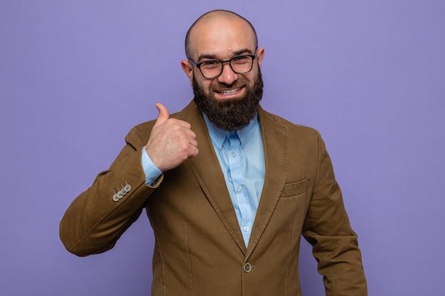 Szczęśliwy brodaty mężczyzna w brązowym garniturze w okularach, patrzący w kamerę, uśmiechający się radośnie pokazując kciuk do góry stojący na fioletowym tle