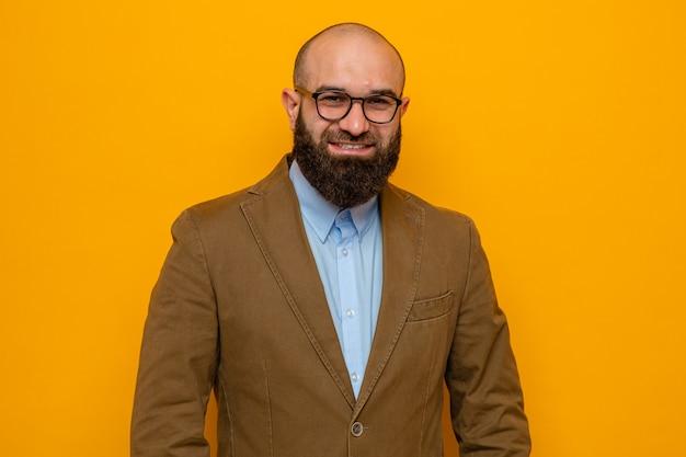 Szczęśliwy brodaty mężczyzna w brązowym garniturze w okularach, uśmiechający się radośnie