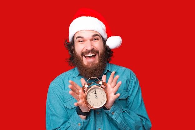Szczęśliwy brodaty mężczyzna w czapce świętego mikołaja trzymający budzik o godzinie 12