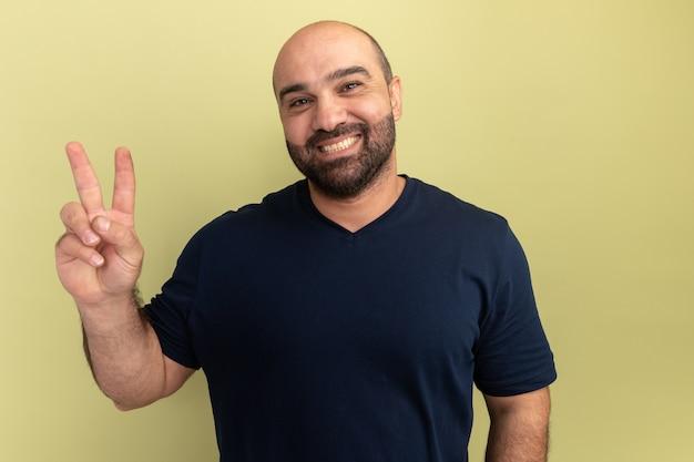 Szczęśliwy brodaty mężczyzna w czarnej koszulce uśmiecha się radośnie pokazując znak v stojący nad zieloną ścianą
