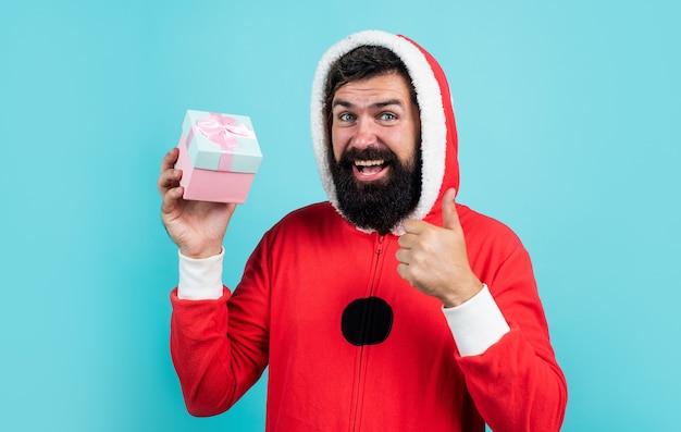 Szczęśliwy brodaty mężczyzna w stroju świętego mikołaja z obecnym pudełkiem świętować nowy rok ferie zimowe, wyprzedaże świąteczne.